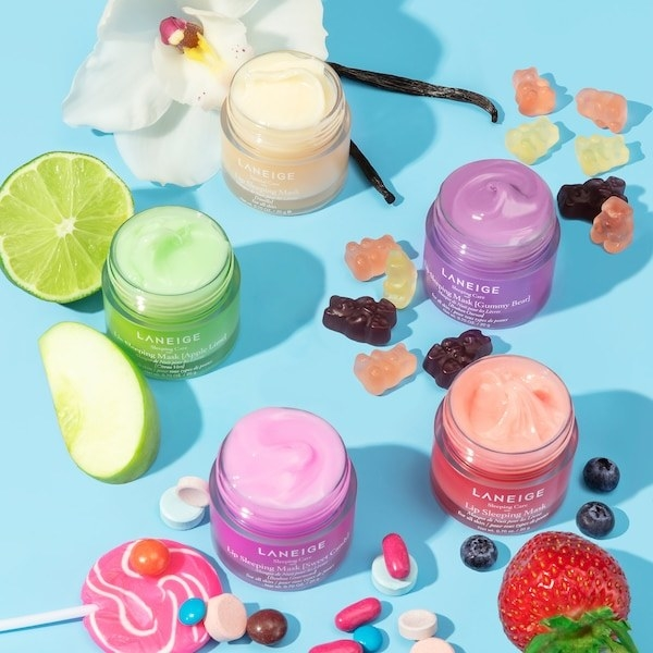 Multiple jars of the lip mask shown with candies and fruit scattered around them