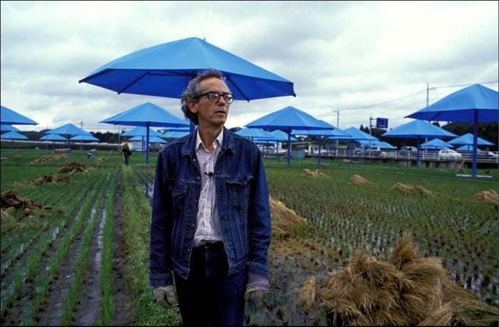Man in denim jacket in a field with blue umbrellas behind him