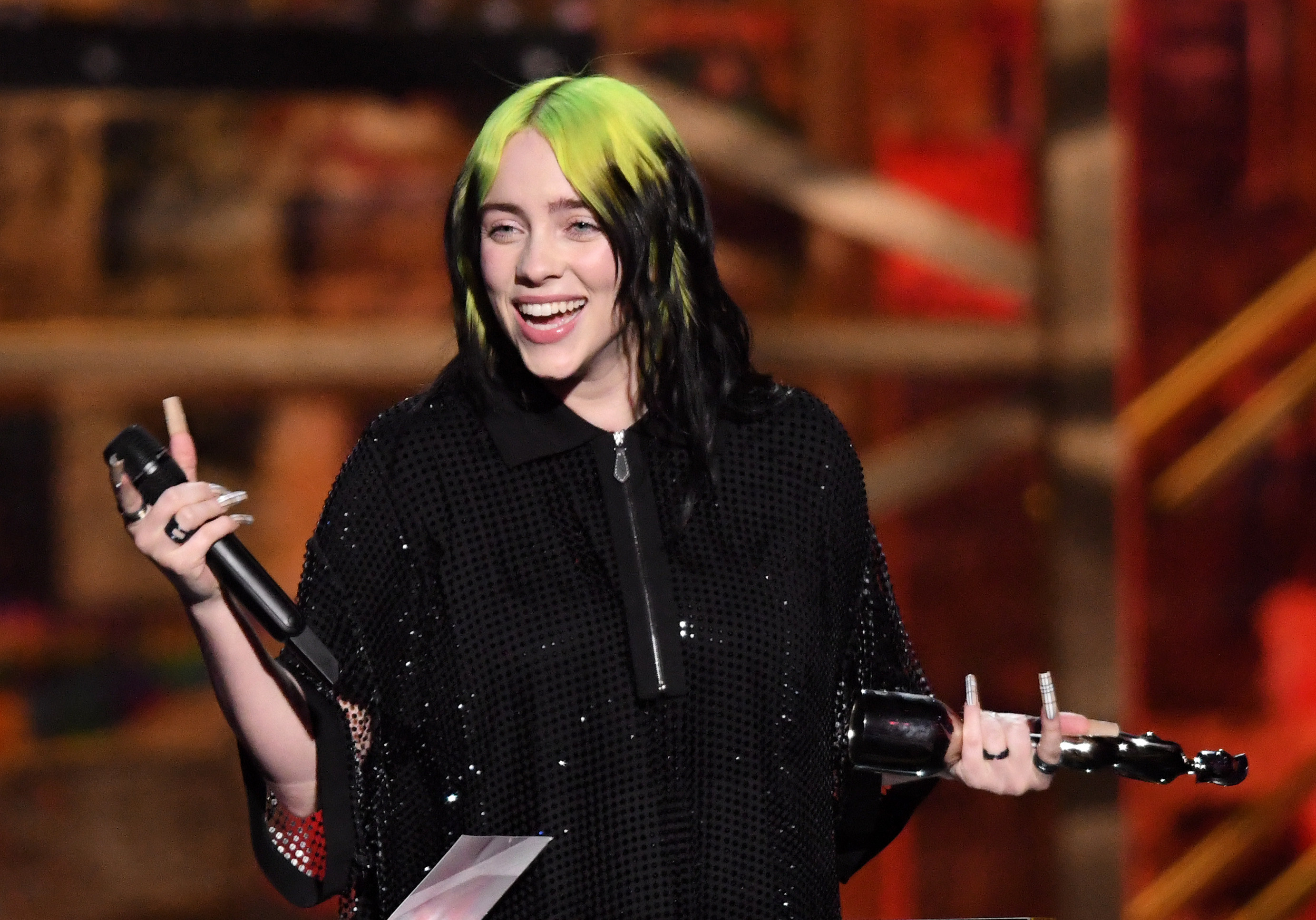 Billie Eilish smiling, holding a microphone and an award
