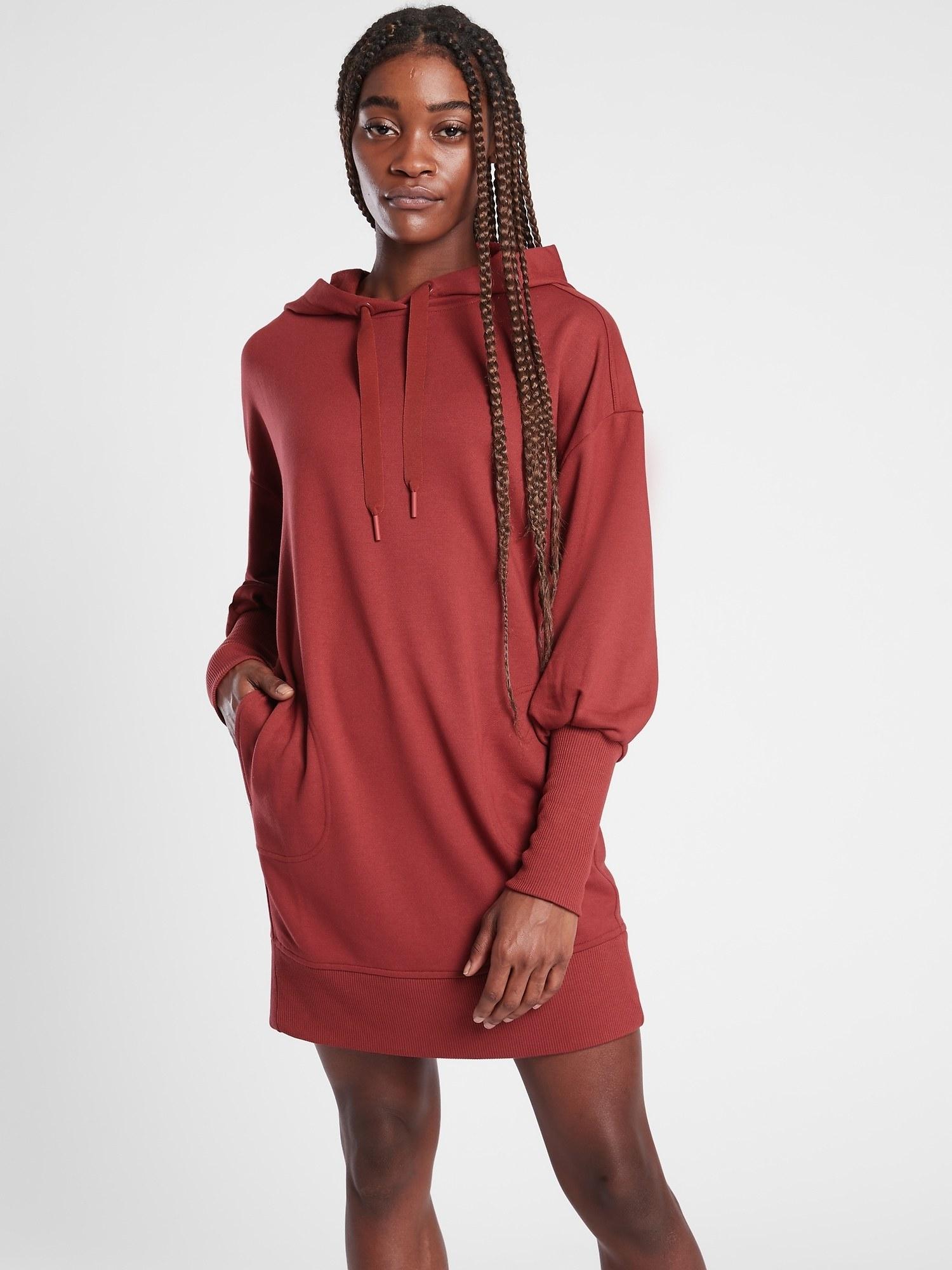 a model in a red long sleeve hoodie dress