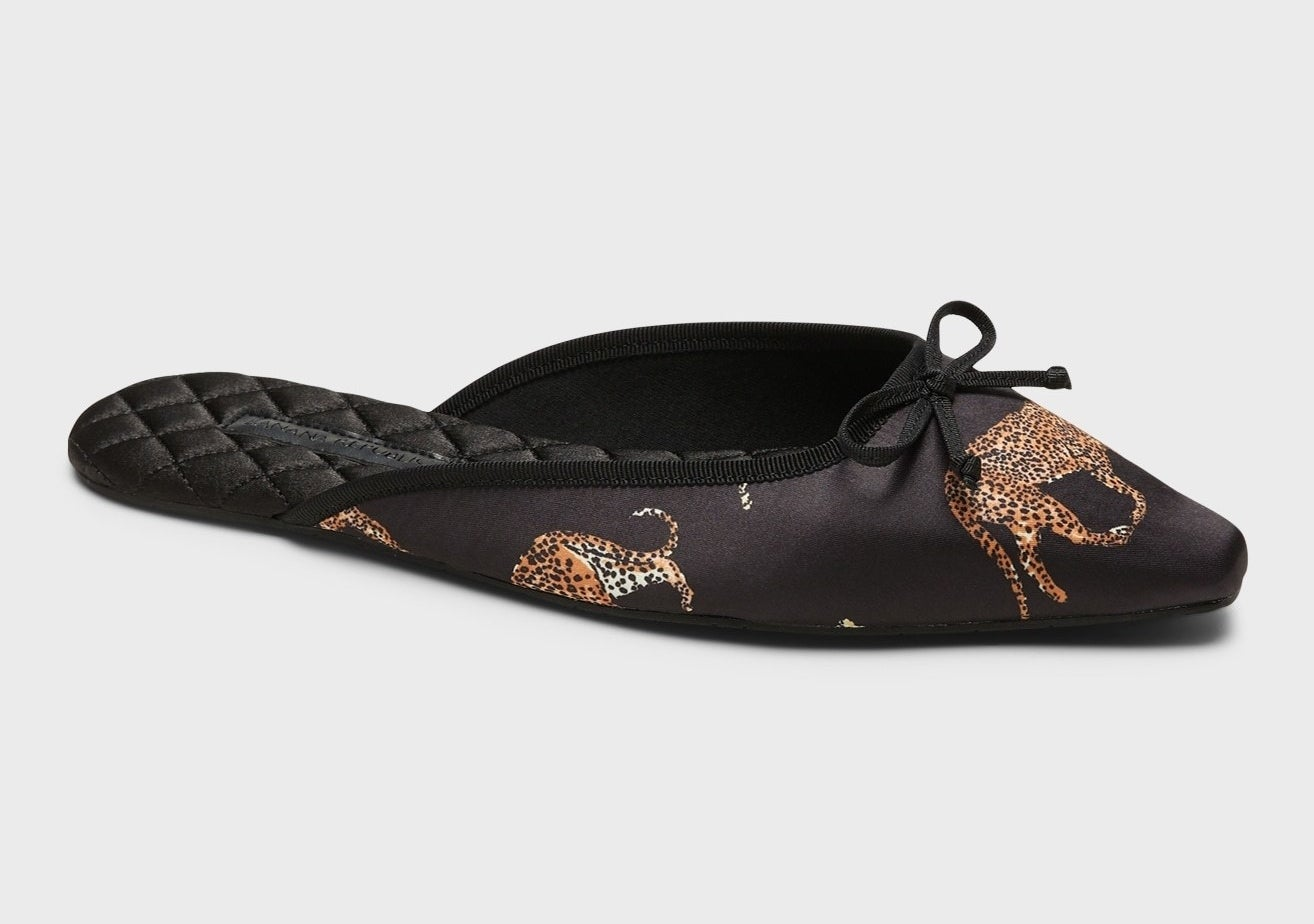 a black pointed slipper with a thin bow on it and a cheetah on it