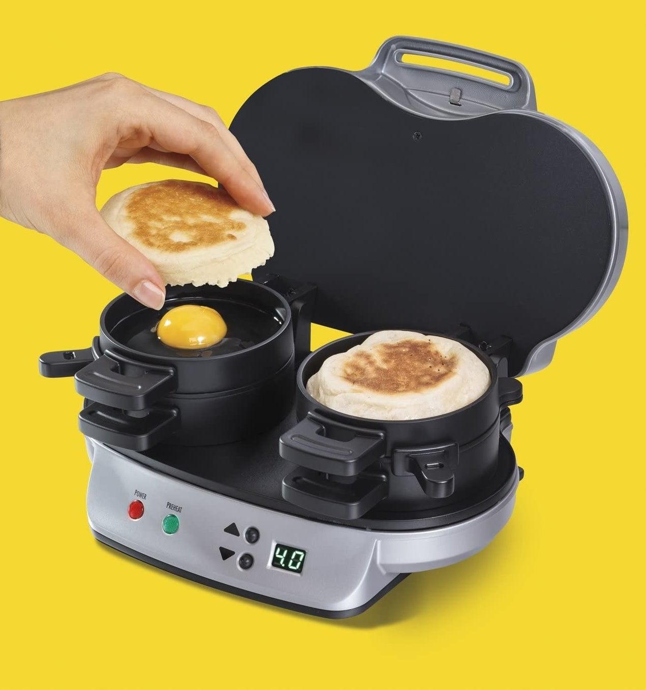 A person making a breakfast sandwich in the breakfast sandwich maker