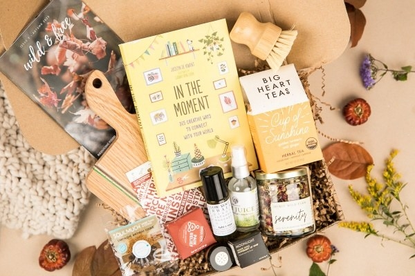 an activity book, box of tea, eco dish scrubber, and other wellness items