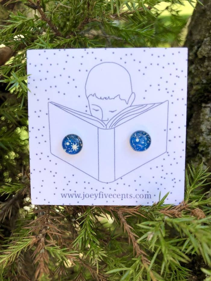 a pair of blue and white celestial stud earrings with pine tree branches