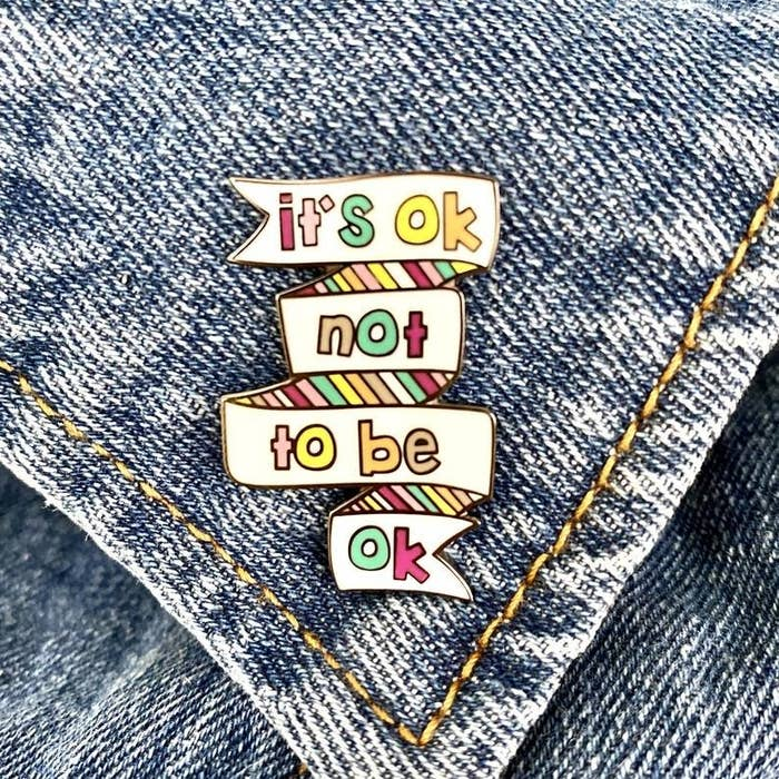 """a pin that says """"it's ok not to be ok"""" in rainbow lettering"""