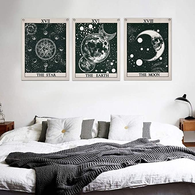 tarot tapestries of a star, earth, the moon hung on a wall