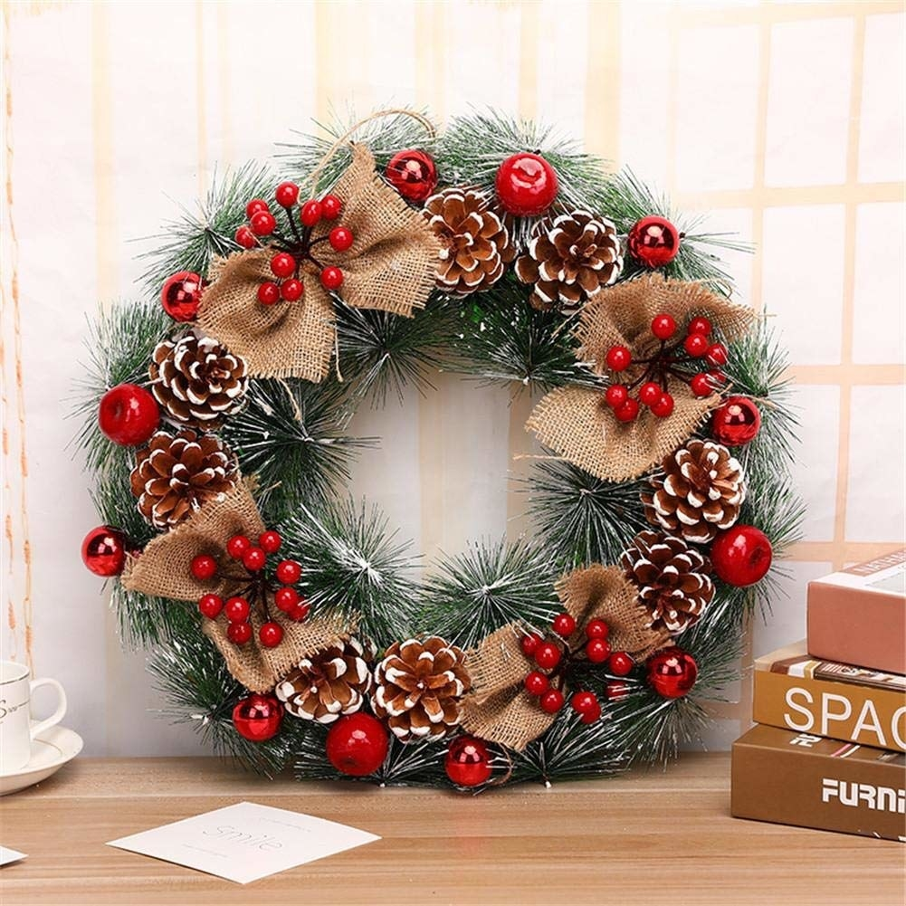 A stunning wreath with white dusted fake pine, burlap bows, holly berries, cherries and pine cone flowers.