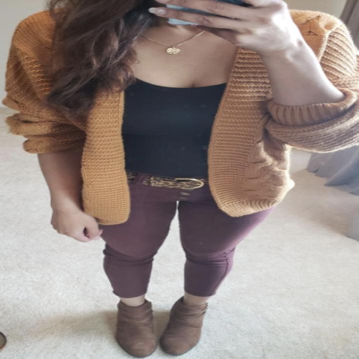 Reviewer wearing mustard cardigan