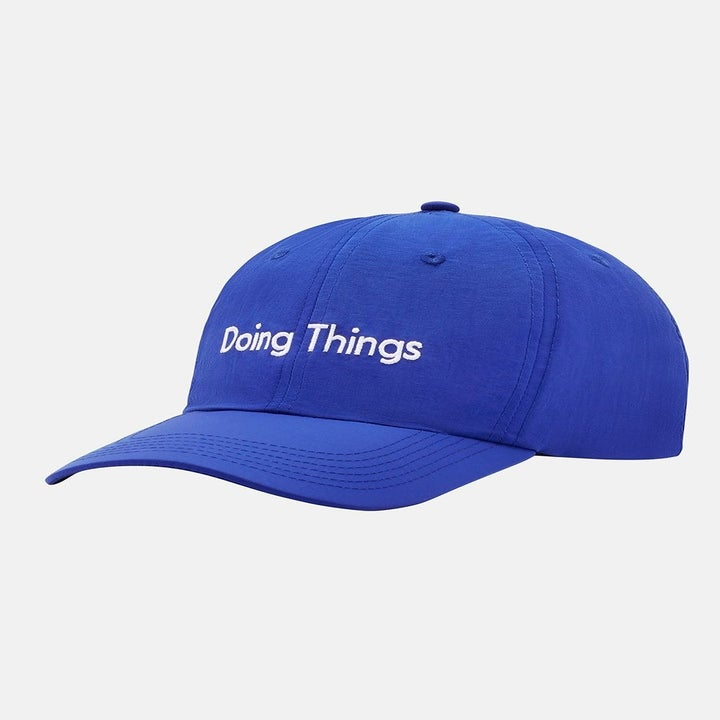 """Front view of the blue hat which says """"Doing things"""""""