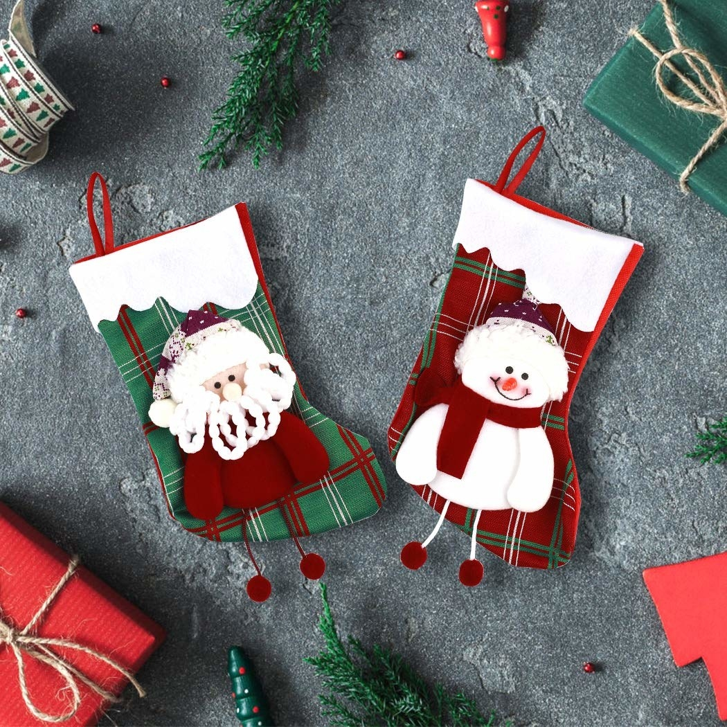 A set of green and red plaid stockings with a Santa and a snowman on them.