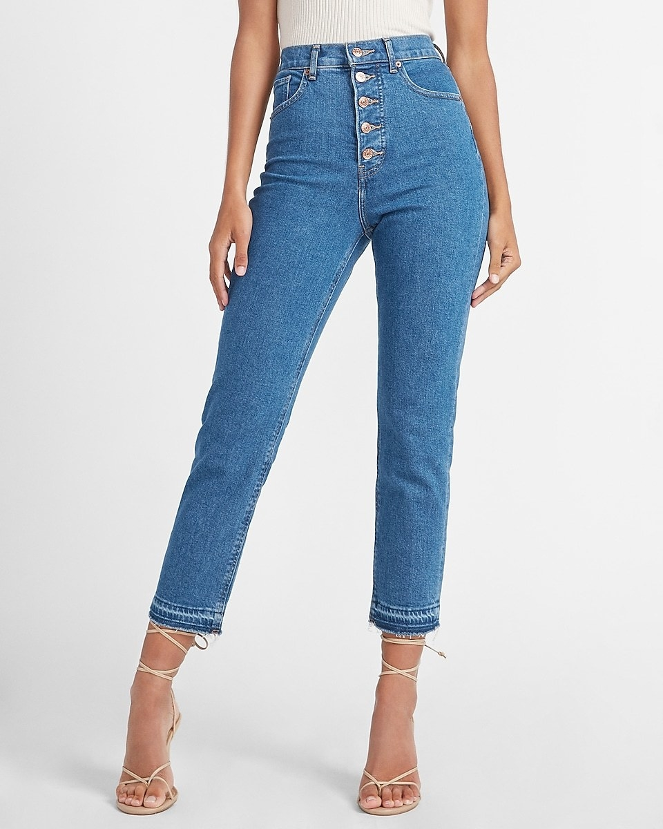 model wearing button-fly high waisted jeans