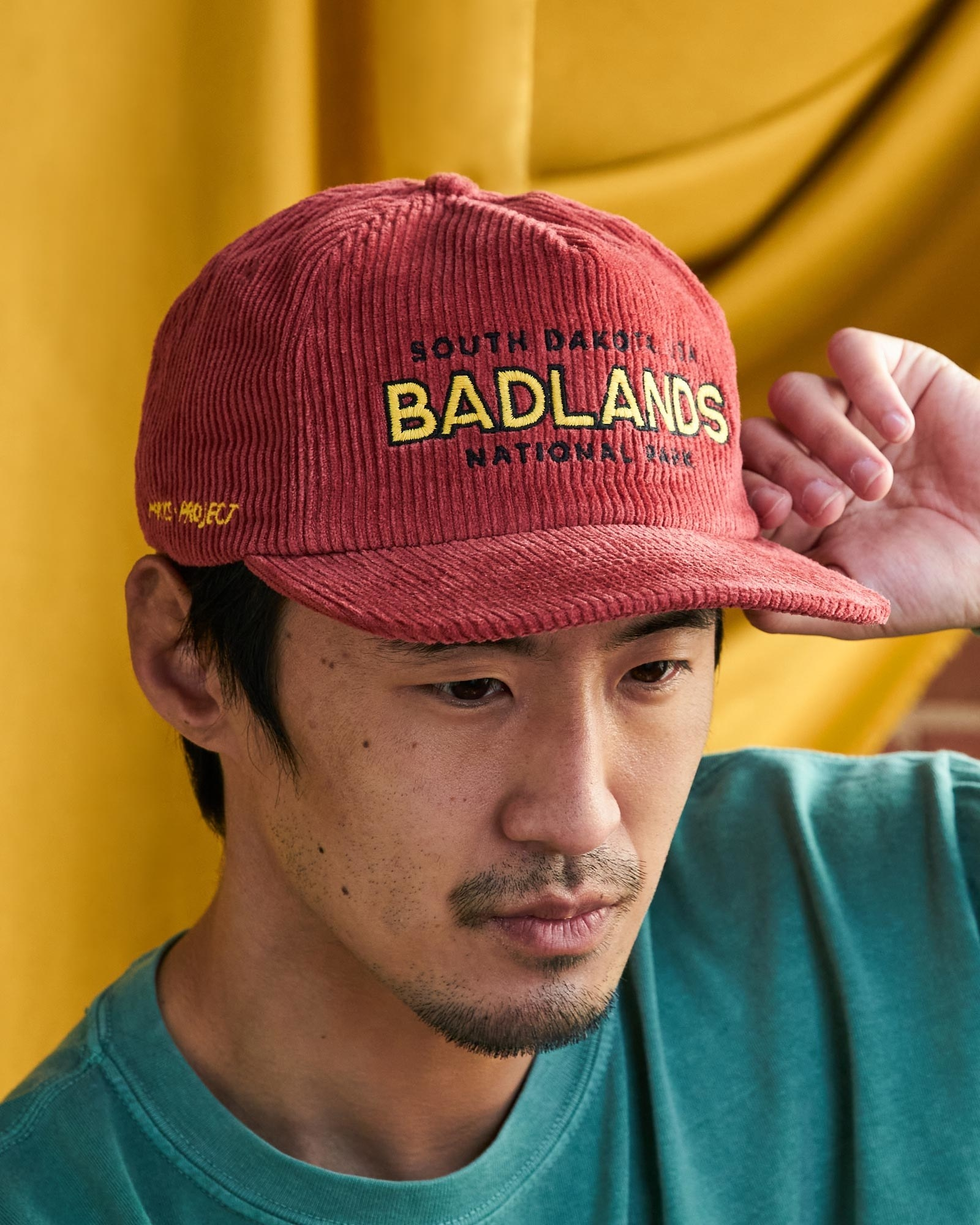 "Model wearing red cord hat with ""South Dakota Badlands National Park"" embroidered onto it"