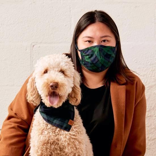 model wearing a plaid mask and dog wearing a matching bandana