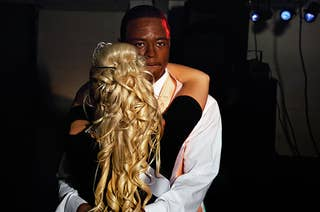 The back of a girl's head and a young man looking past the camera as they dance.