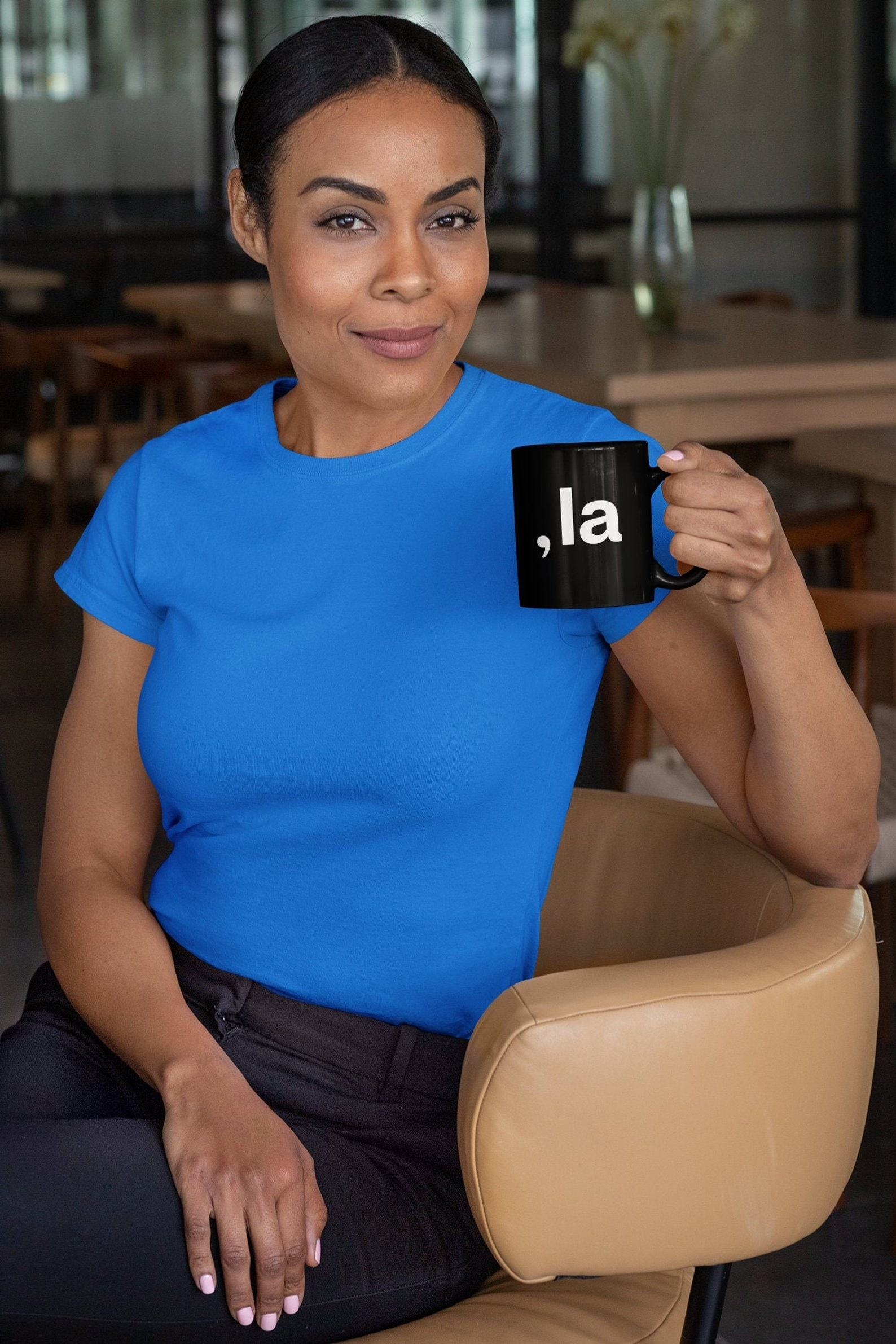 """A black mug with a white comma and the word """"la"""" as a Kamala pun"""