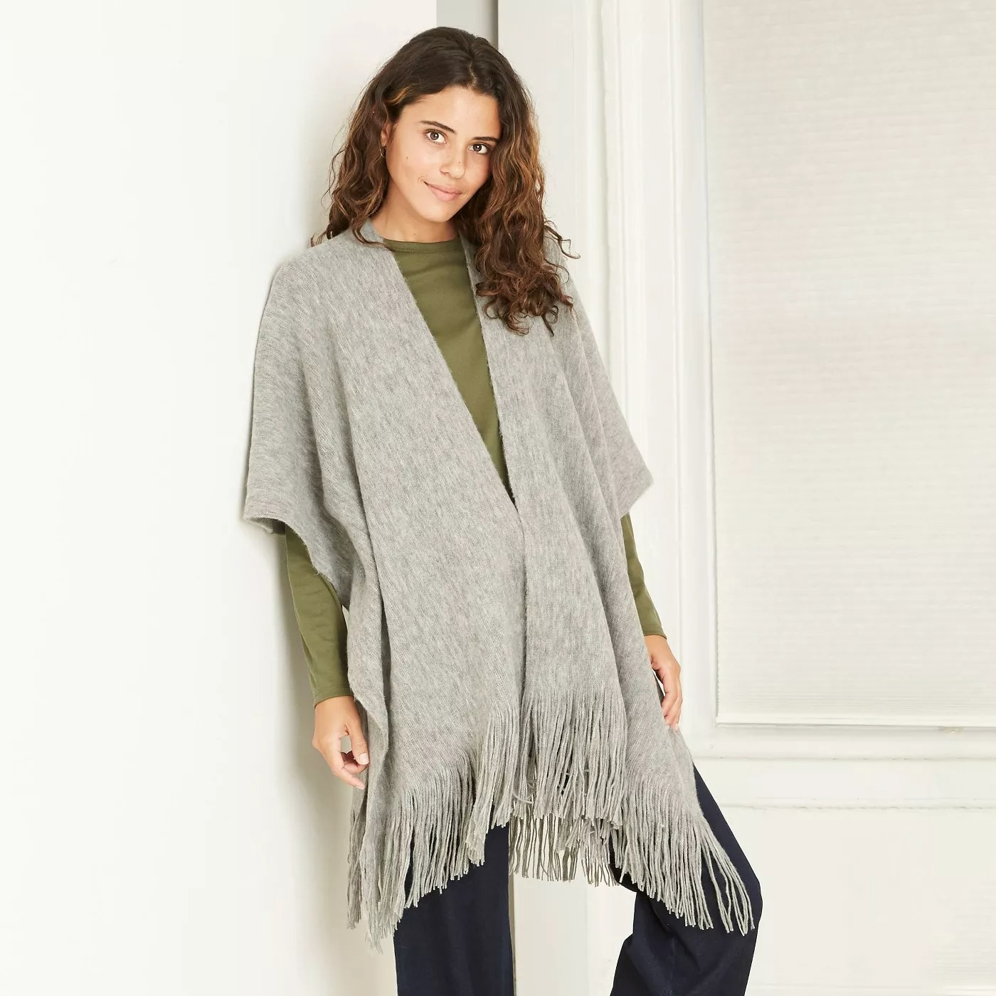 A gray knit poncho with fringe on the bottom.