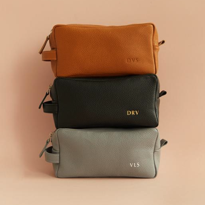 A close-up of three differently colored men's grooming bags, all stacked on each other