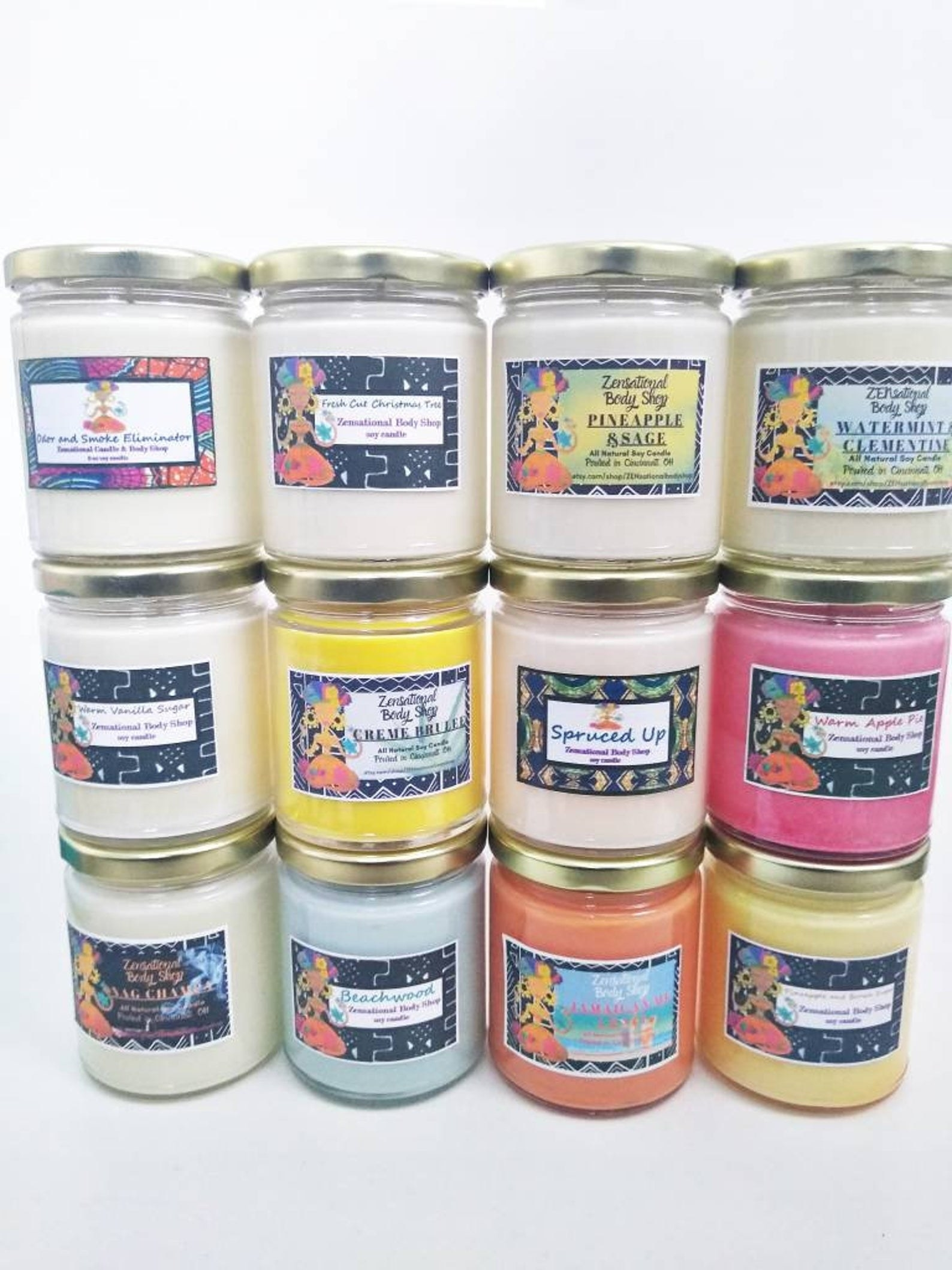 """12 different candles in various colors with illustrated labels on them and flavors like """"pineapple and sage"""" or """"spruced up"""""""