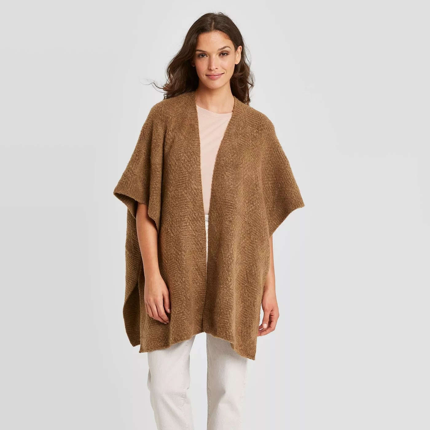 A fuzzy camel colored kimono  paired with basic khaki pants and a white shirt.