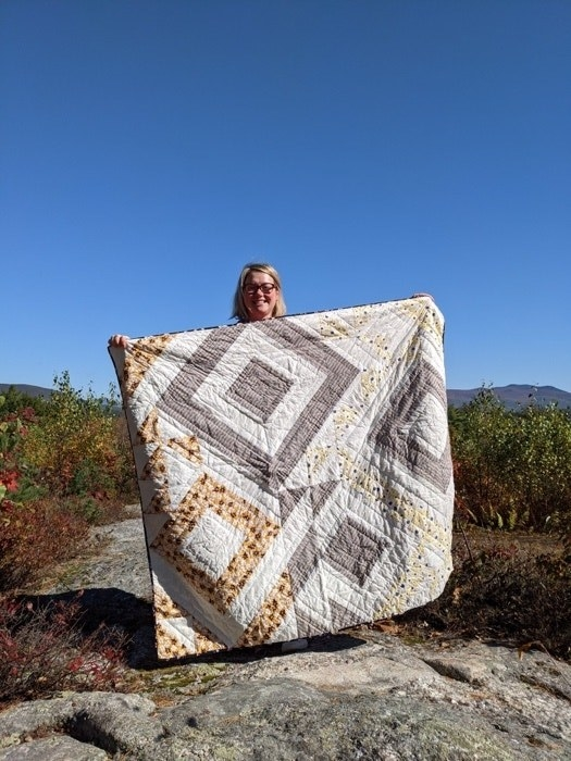 A blonde woman holding up her handmade quilt