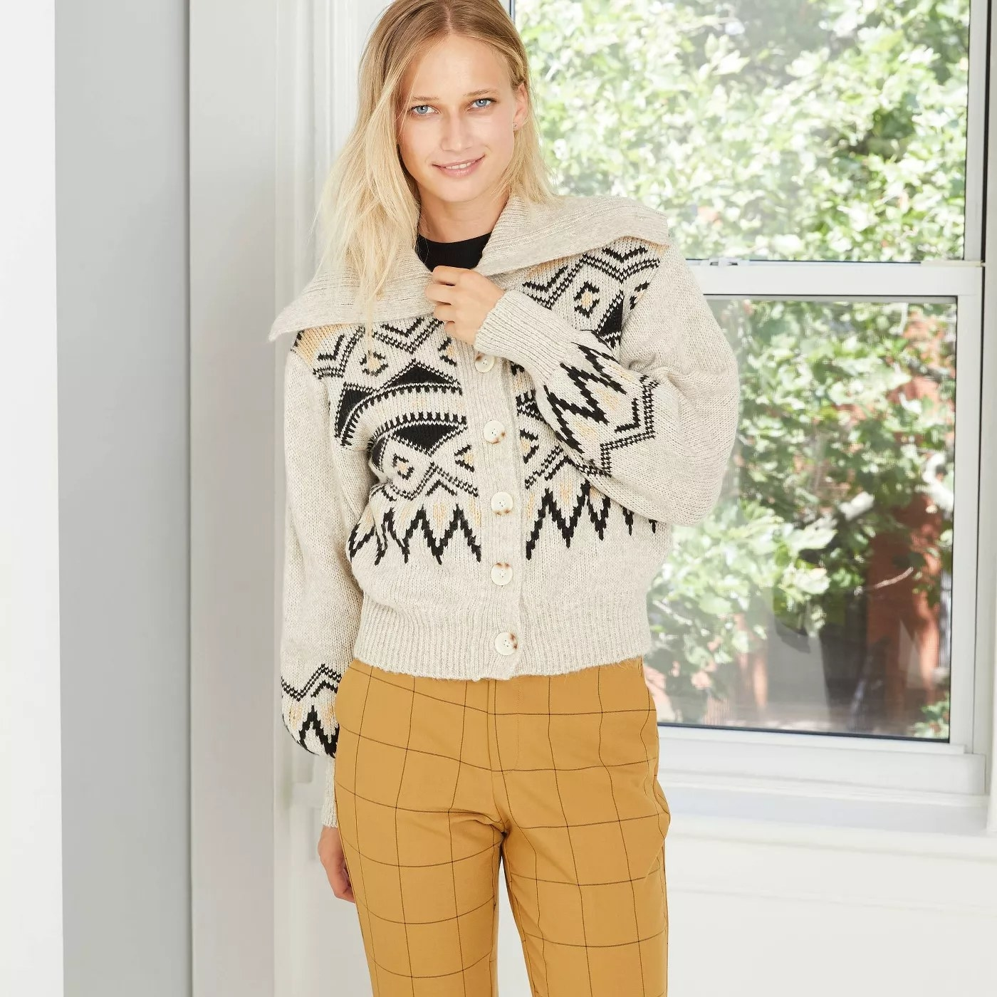 A buttoned off-white sweater with a black triangular pattern paired with mustard yellow pants.