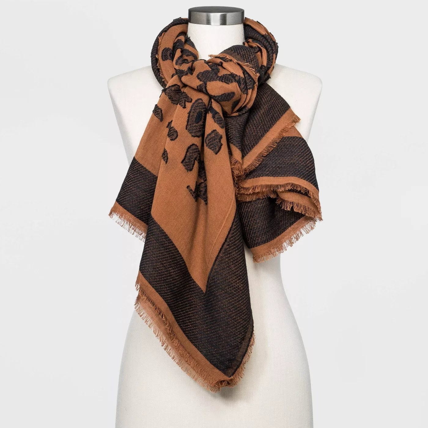 A black and brown scarf that is tied