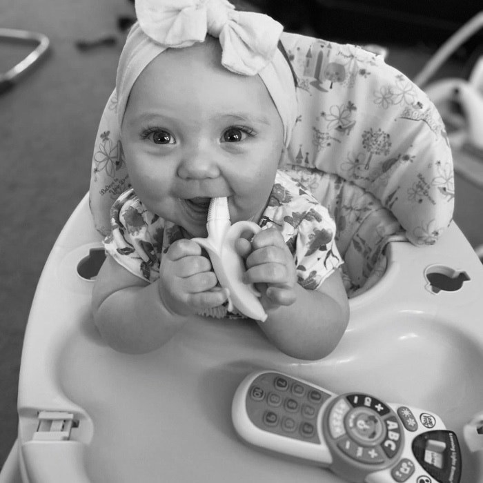 A young baby girl wearing a bow and happily eating a banana