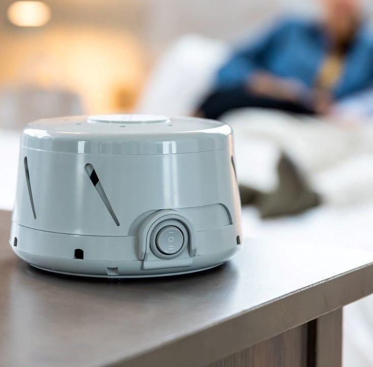 gray white noise machine sitting on top of a bedroom dresser