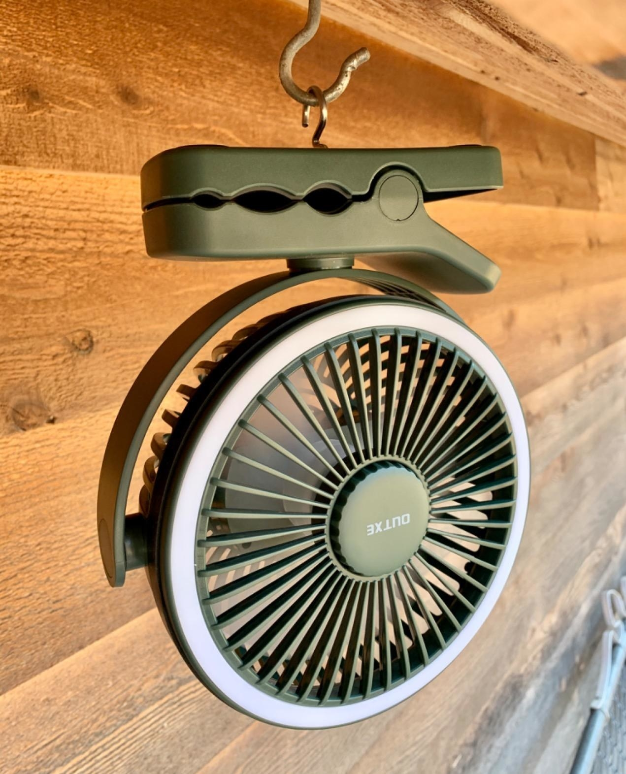A olive colored fan hanging from a hook