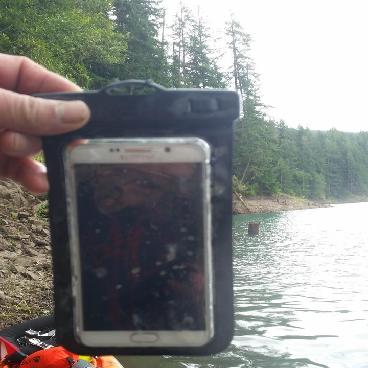 Reviewer holding a phone in the pouch above water