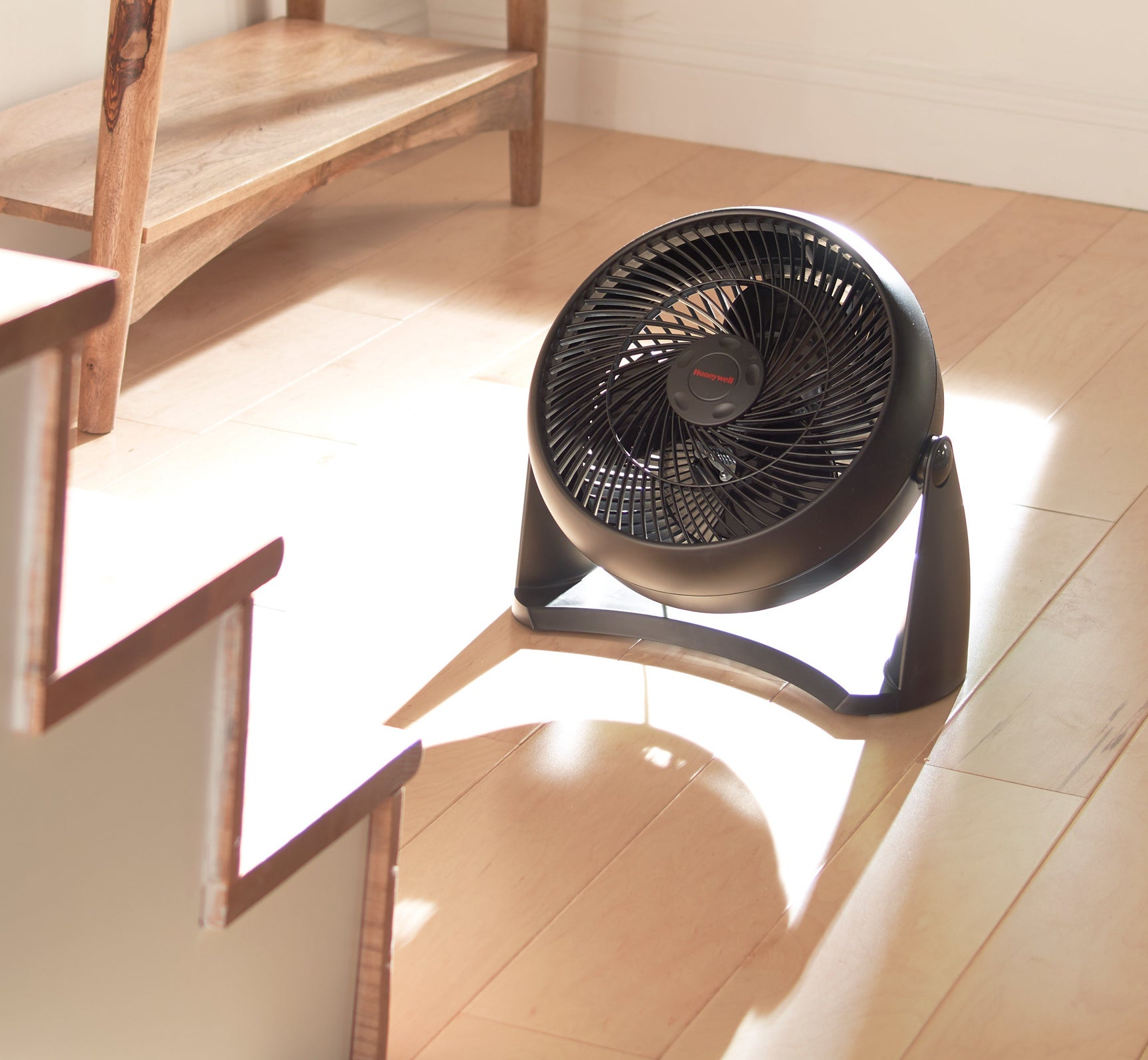 a black fan sitting on the ground of a foyer