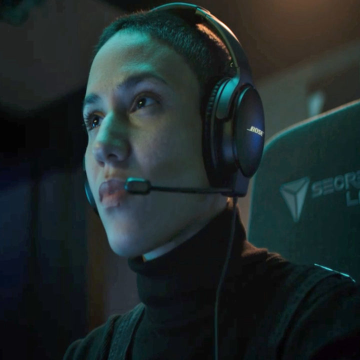 Someone playing video games and wearing their headset in a dark room