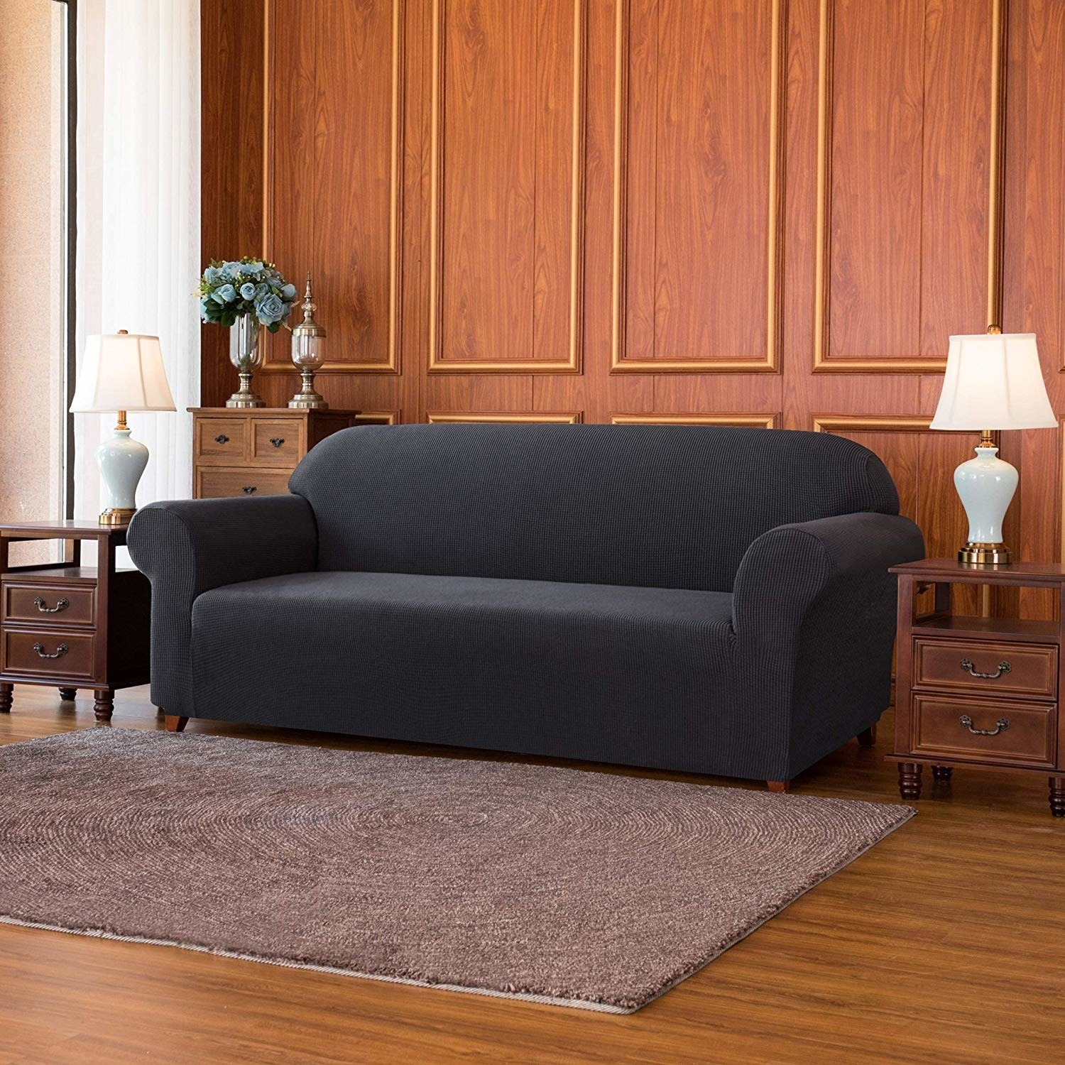 dark dray slipcover over a couch that's sitting in a wood-paneled room