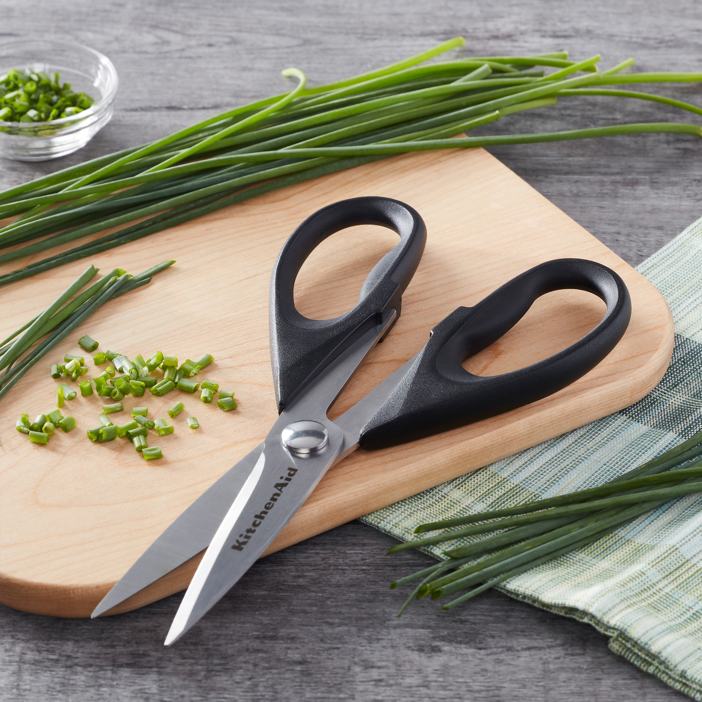 The shears, on a cutting board, shown with herbs