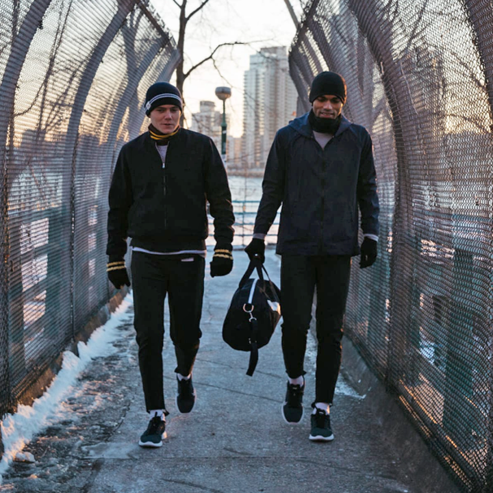 Two men walking outside in the cold, post-workout, carrying the Club Duffel gym bag