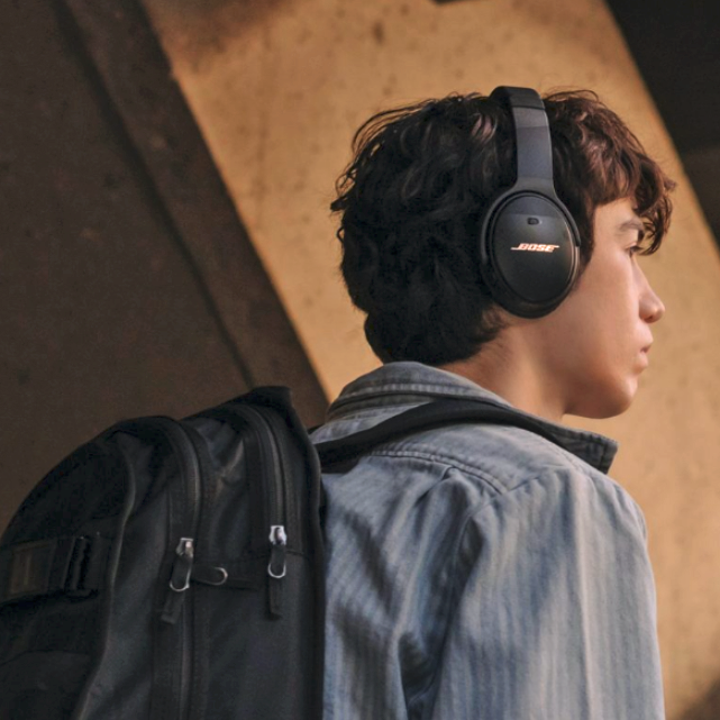 Someone walking down the street while wearing their wireless headphones