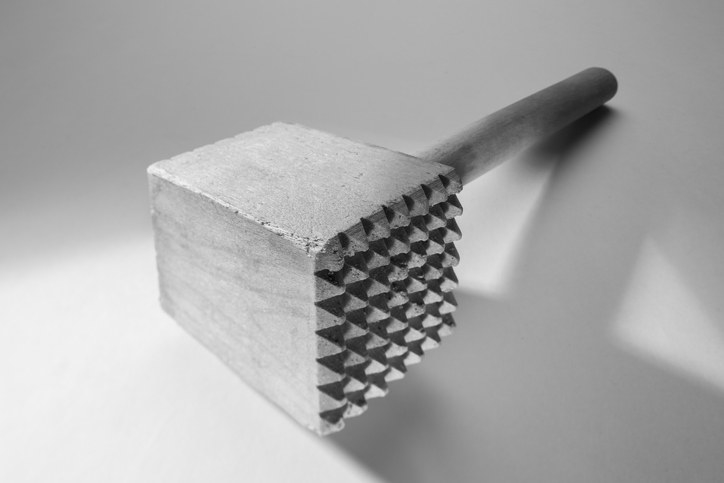 A close-up of an exaggerated perspective of a meat tenderizing mallet.