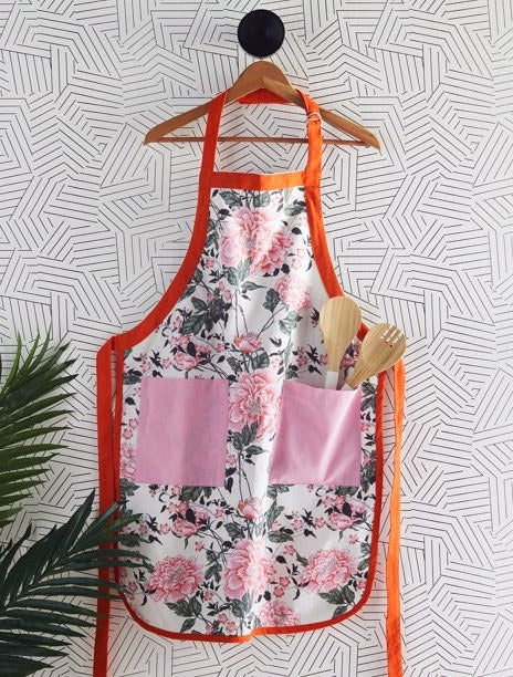 The apron hanging on a patterned wall, with spoons in one of the pockets