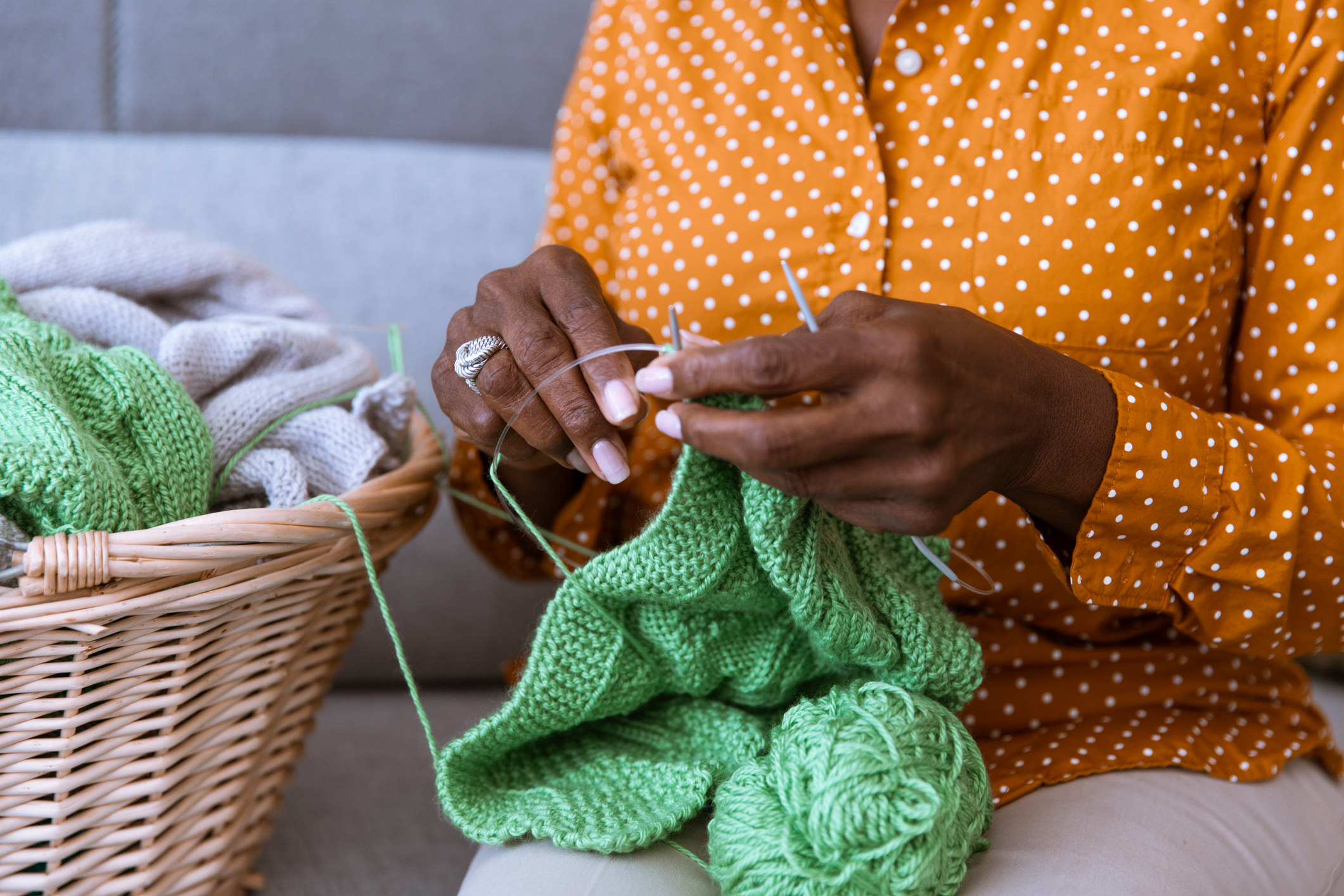 Older woman sitting on a couch and knitting