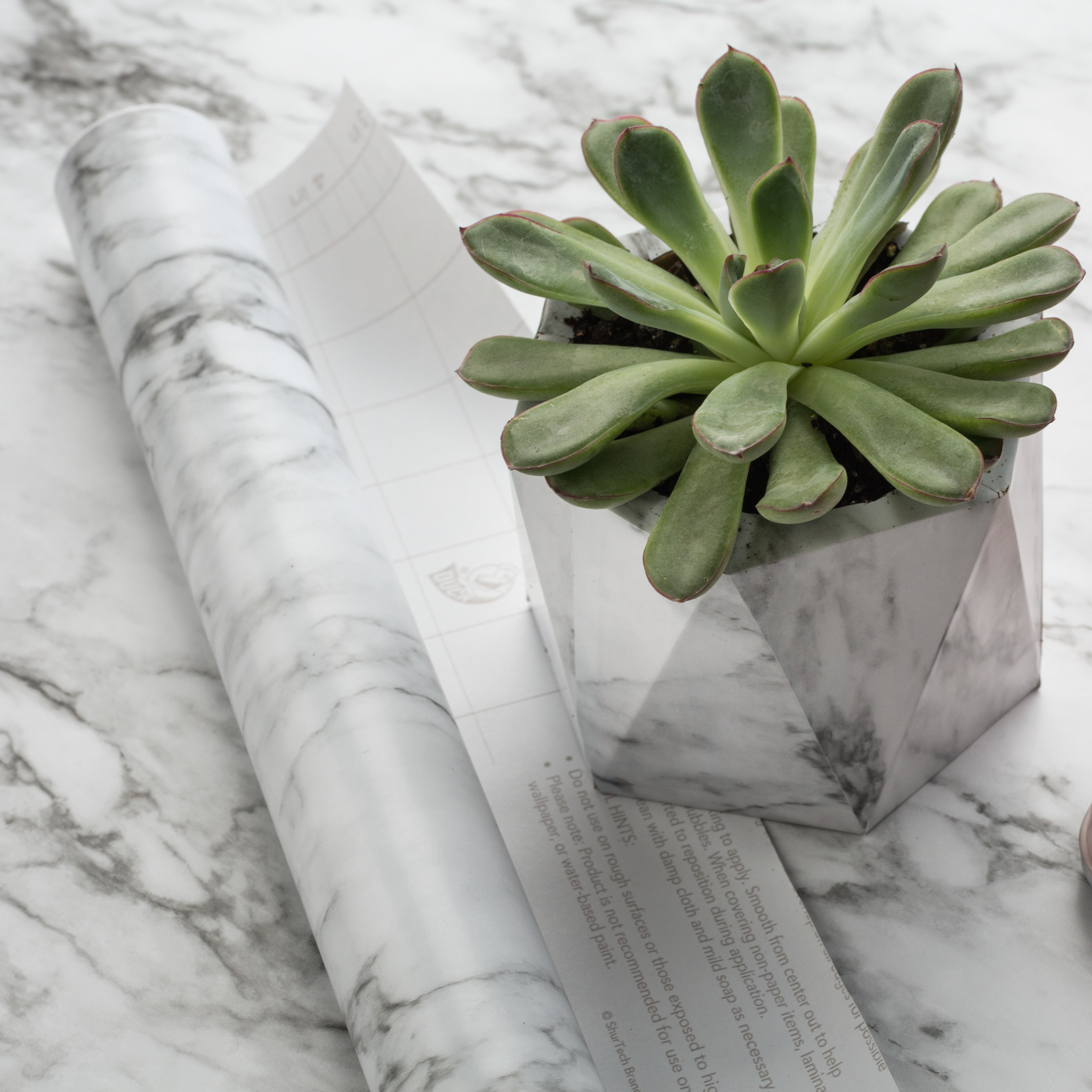 white marble contact paper roll on a white marble countertop