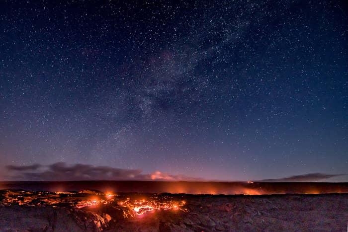 Lava lighting up the sky on a starry night