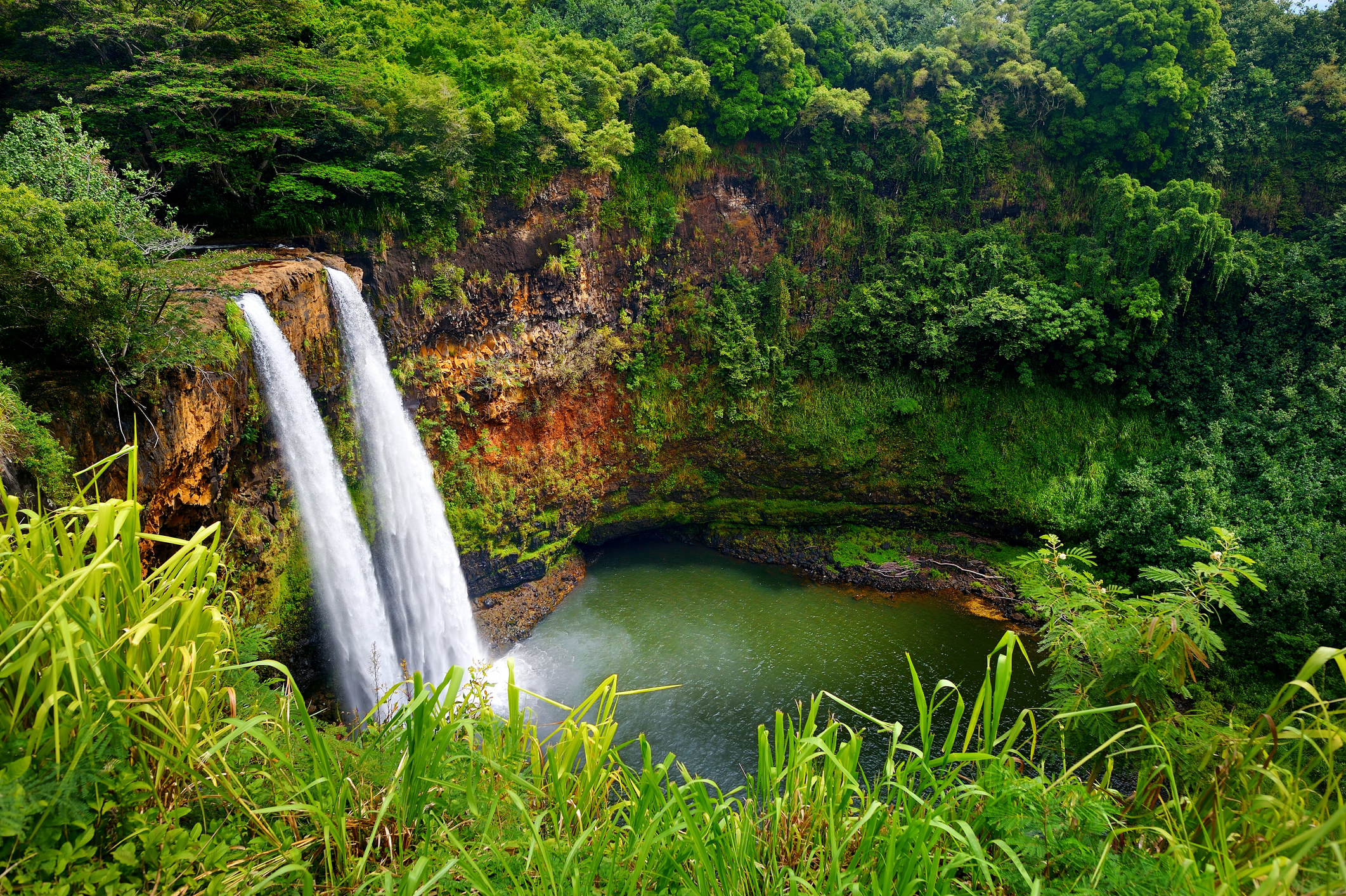 Two waterfalls dropping off a cliff to a pool below