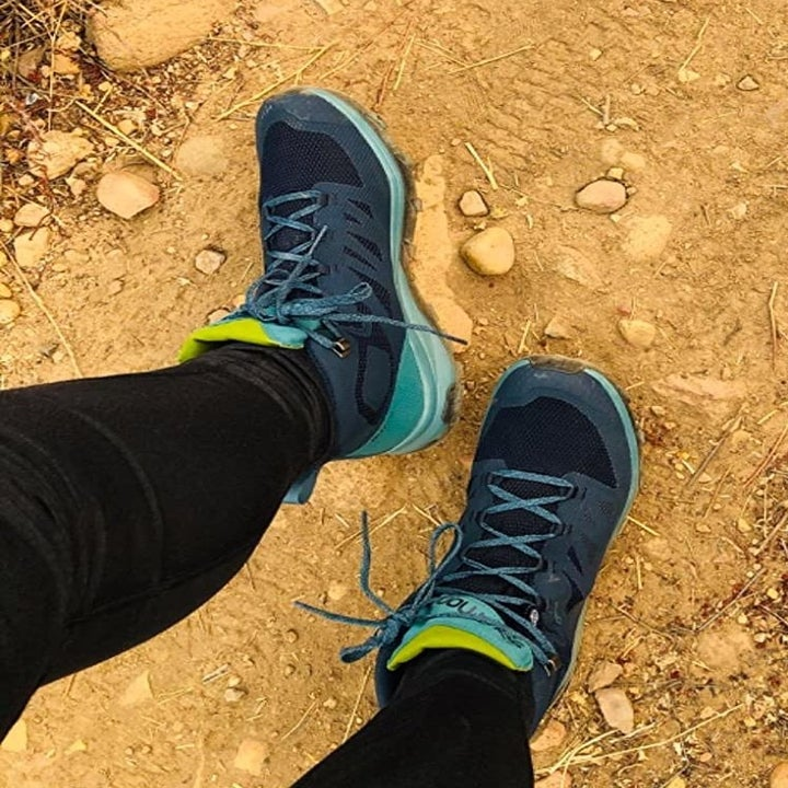 Reviewer wearing teal-colored boots on a rocky hike