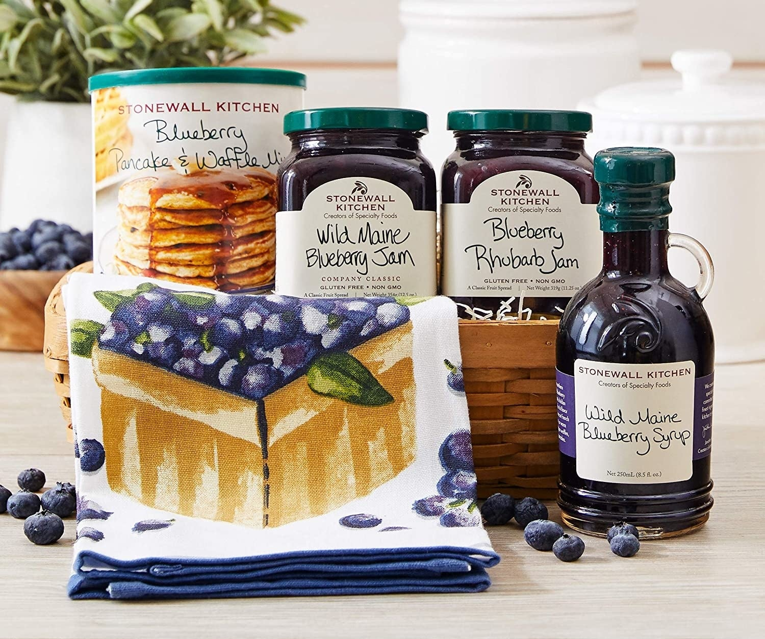 A collection of jams, pancake mix, and maple syrup in a basket with a tea towel