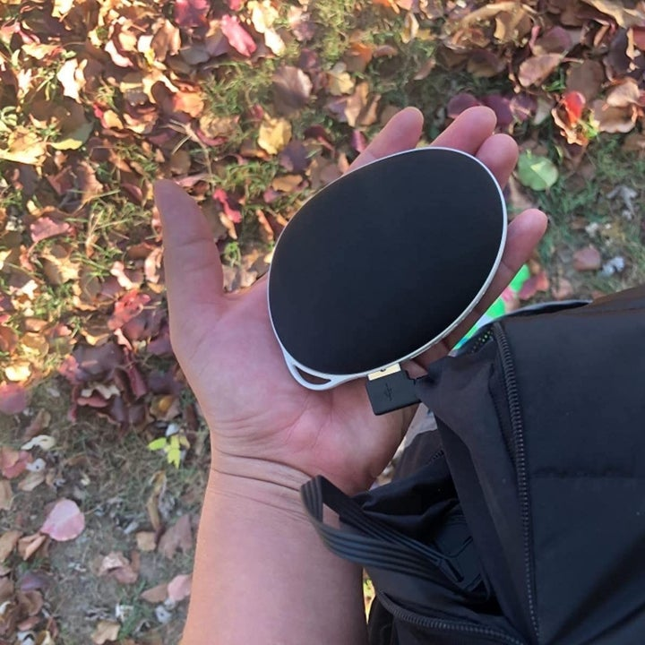 Another reviewer holding the handwarmer clipped onto their bag