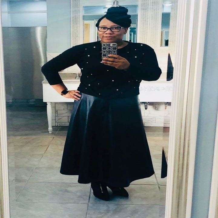 reviewer wearing the black version with a faux leather maxi skirt