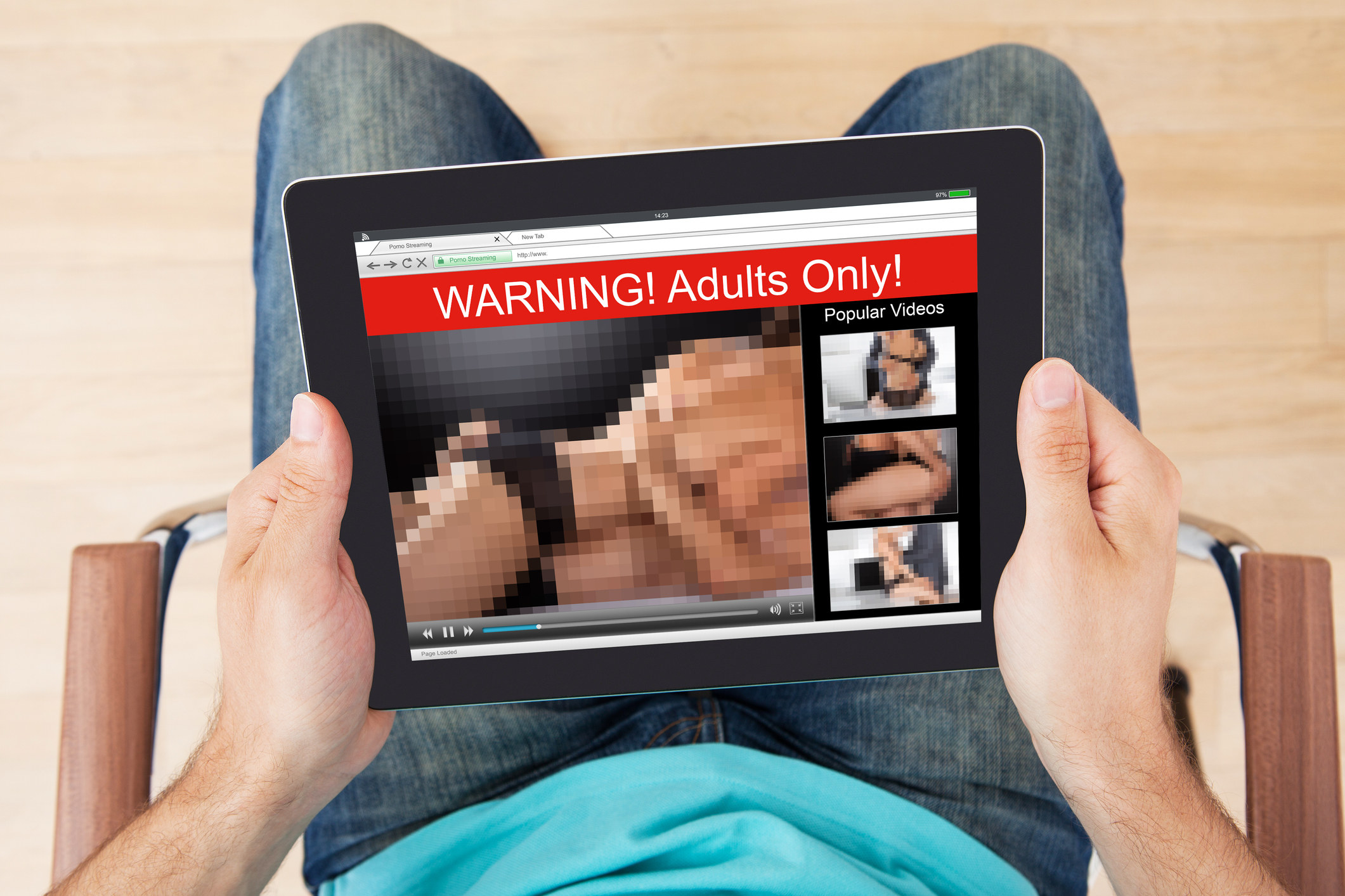 A man looking at porn on a tablet