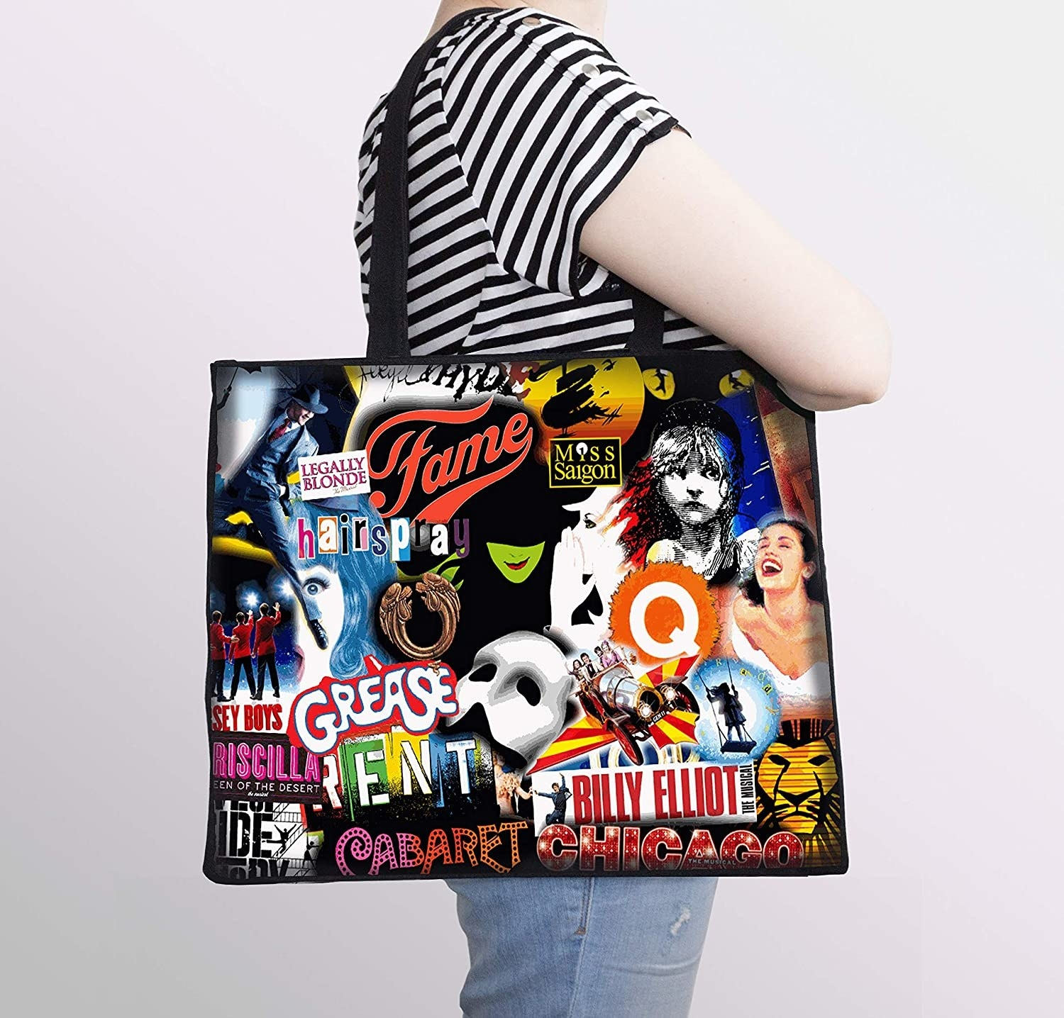 Model wearing the tote bag over their shoulder with logos from a variety of musicals on it