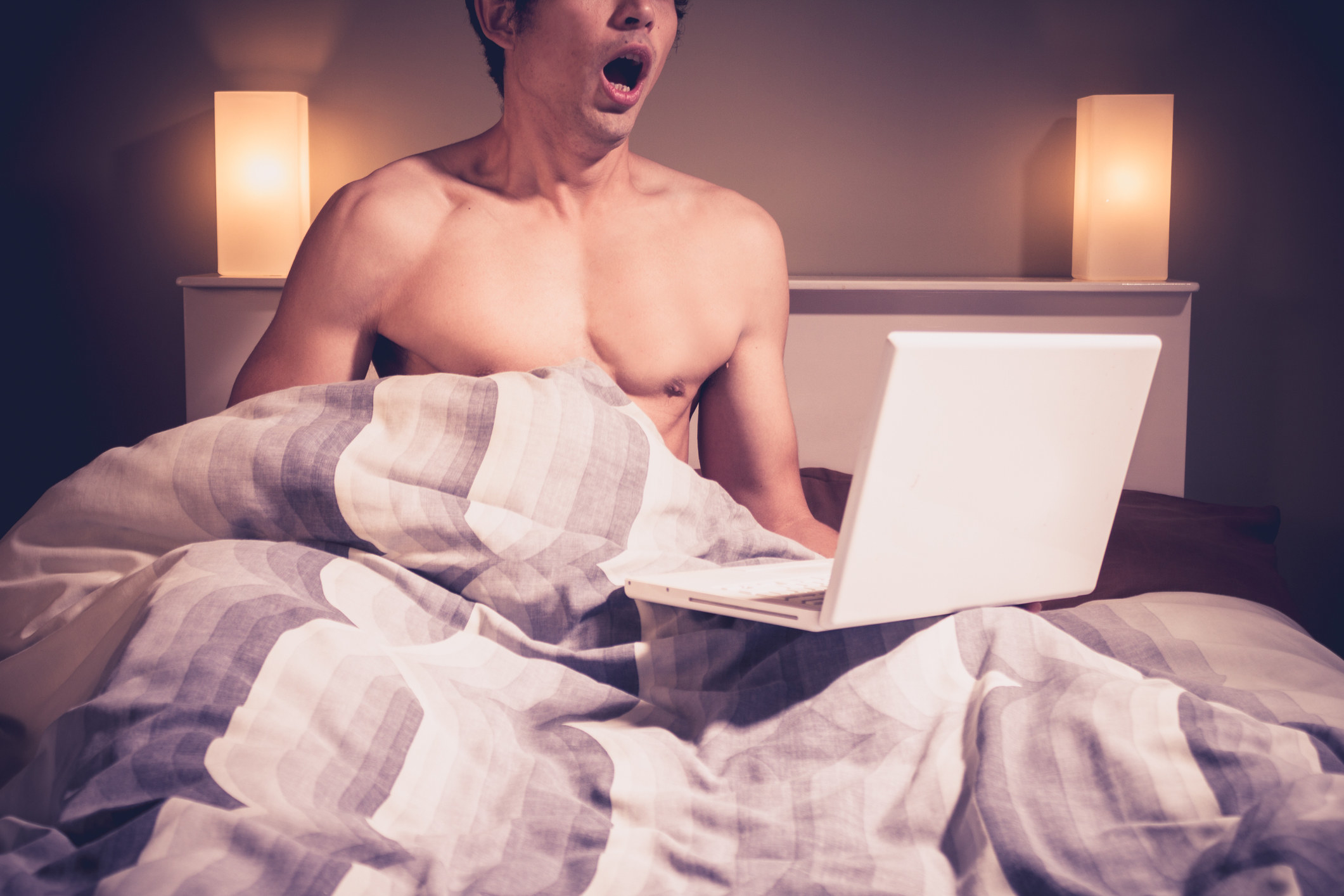 A man in bed with a laptop