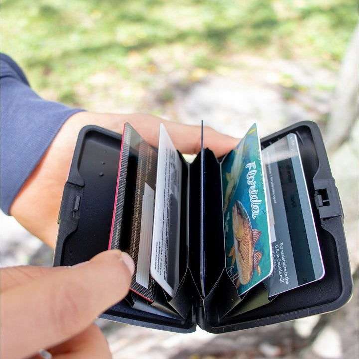 Hand holding open wallet with credit cards inside